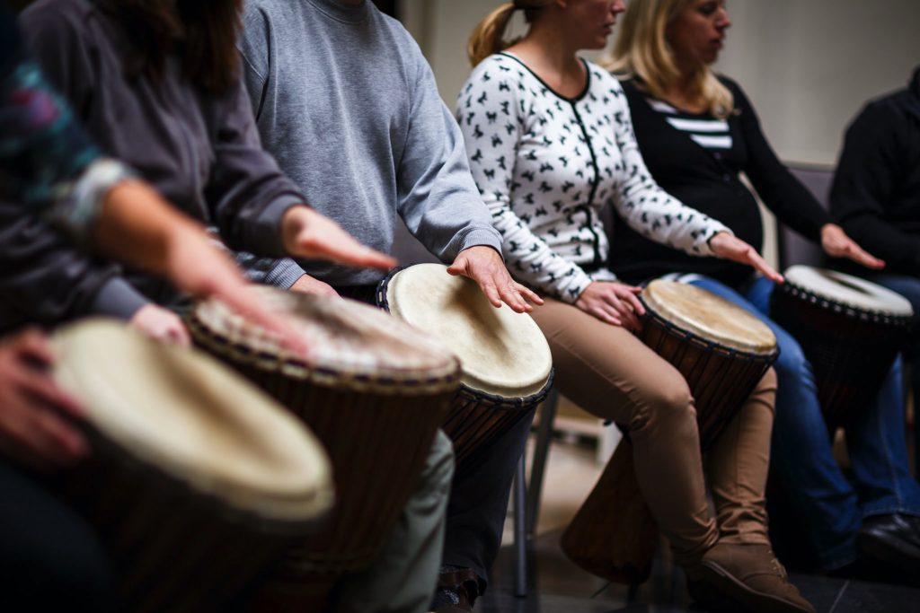 un gruppo di persone sedute e in fila che suonano i tamburi