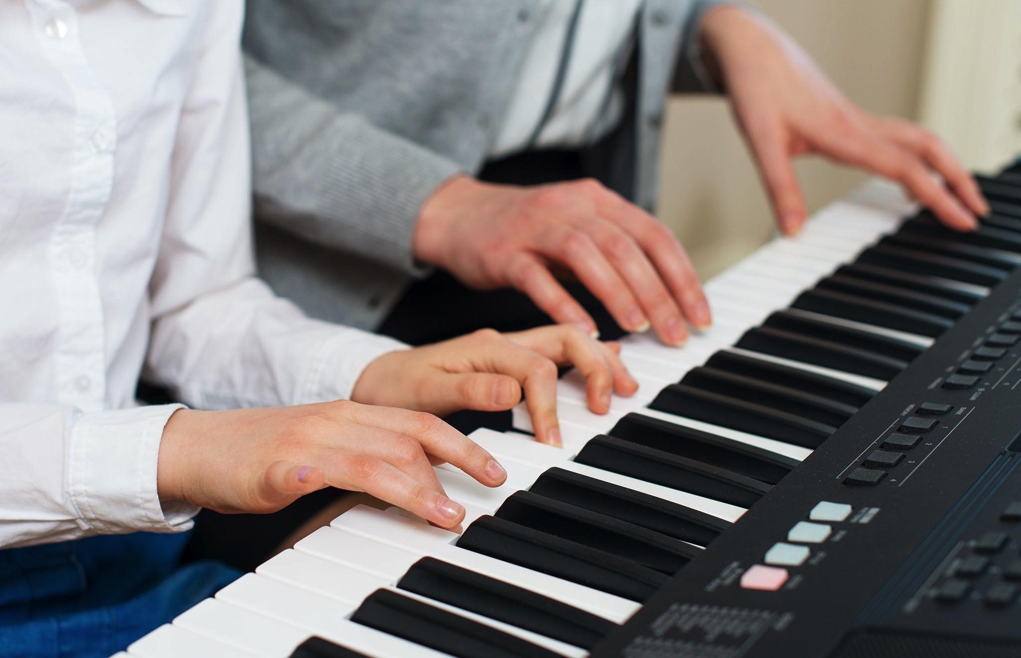 mani di un ragazzo che suona la pianola affiancato da un adulto