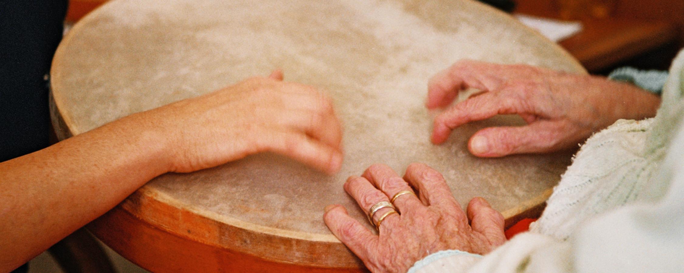 mani di una persona giovane e una anziana che battono su un tamburo
